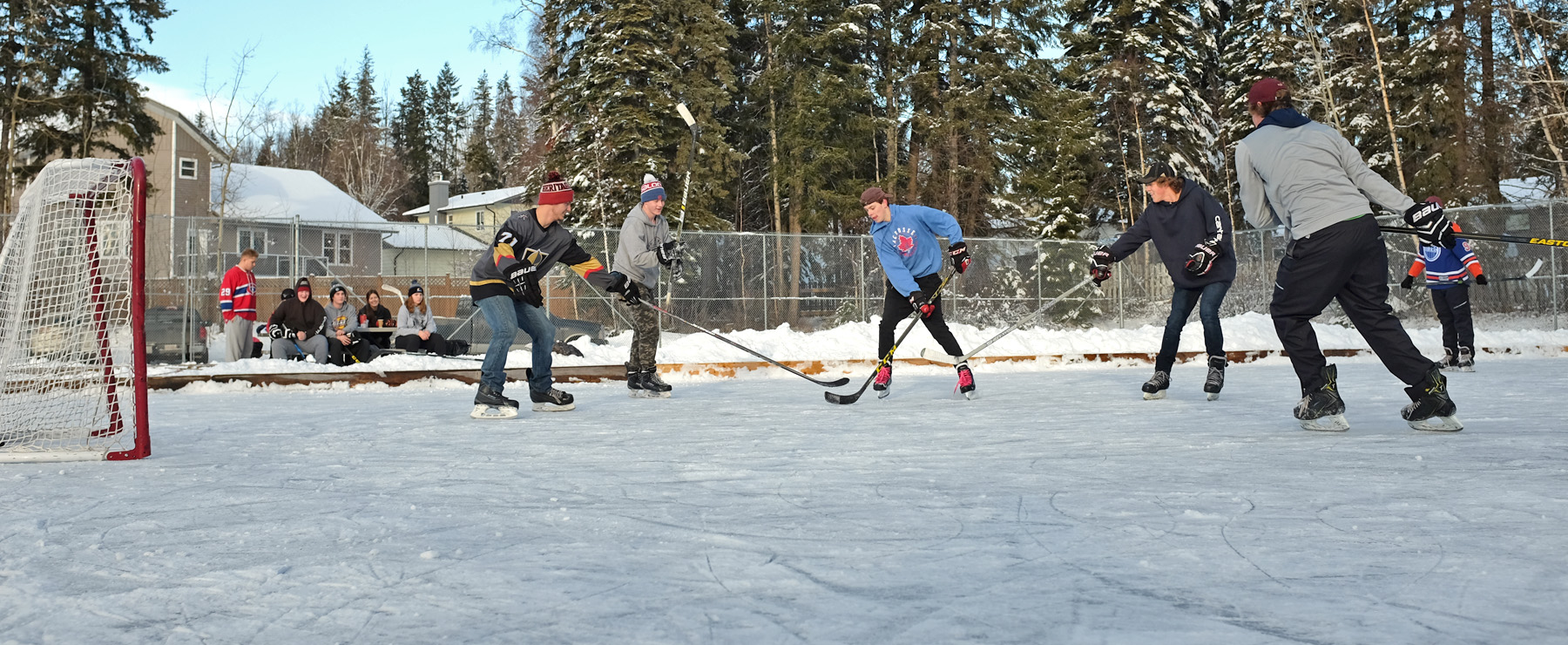 People playing hockey in an outdoor rink