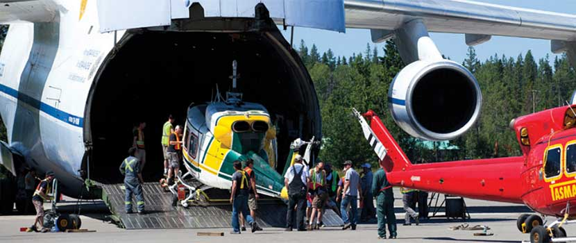 Helicopters being loaded into a transport plane